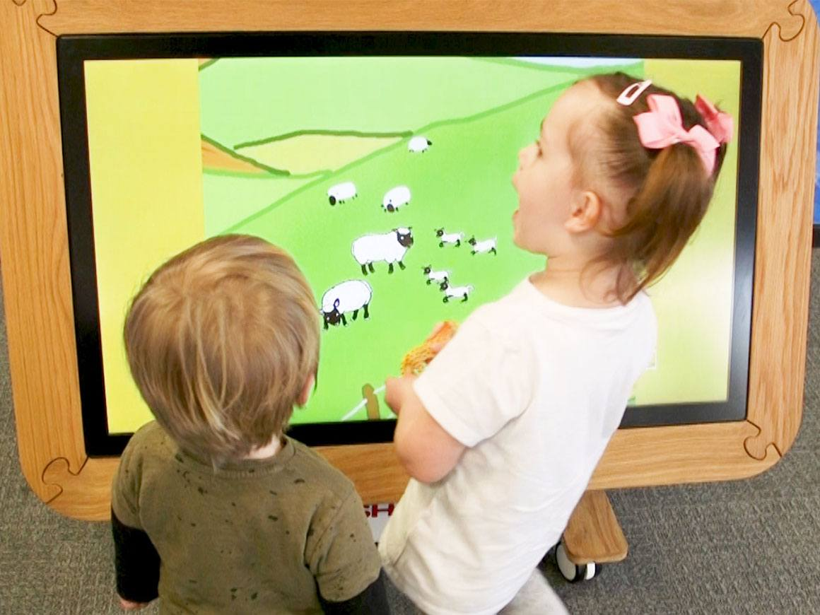 Interactive Touchscreen Table being used by a boy and girl
