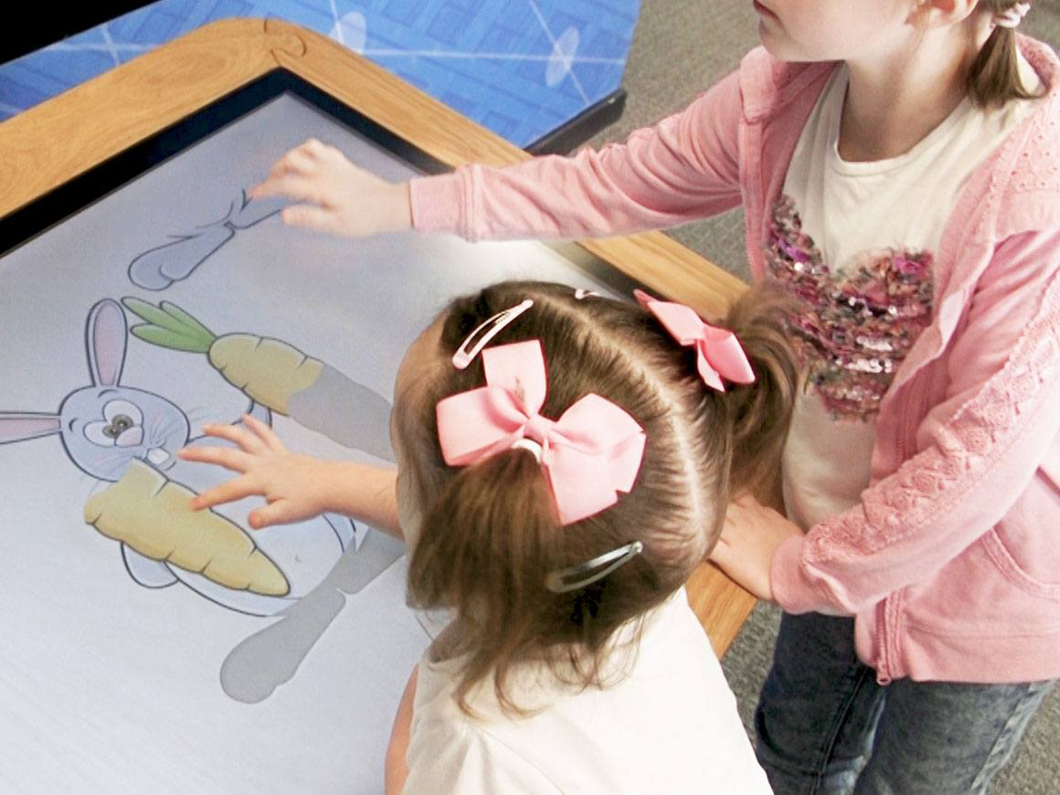 Two girls playing on the Interactive Touchscreen Table